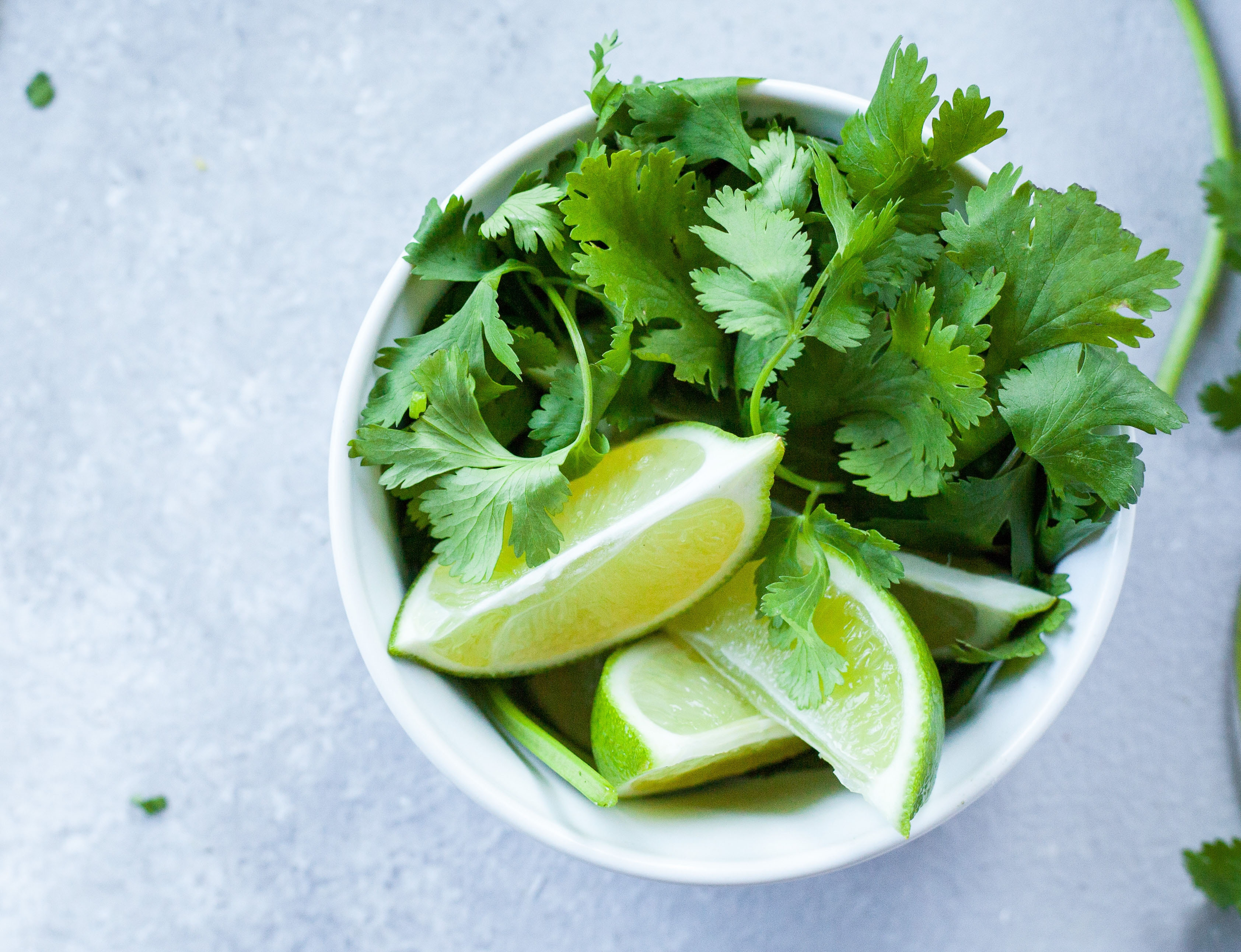 bowl of cilantro leaves and sliced limes