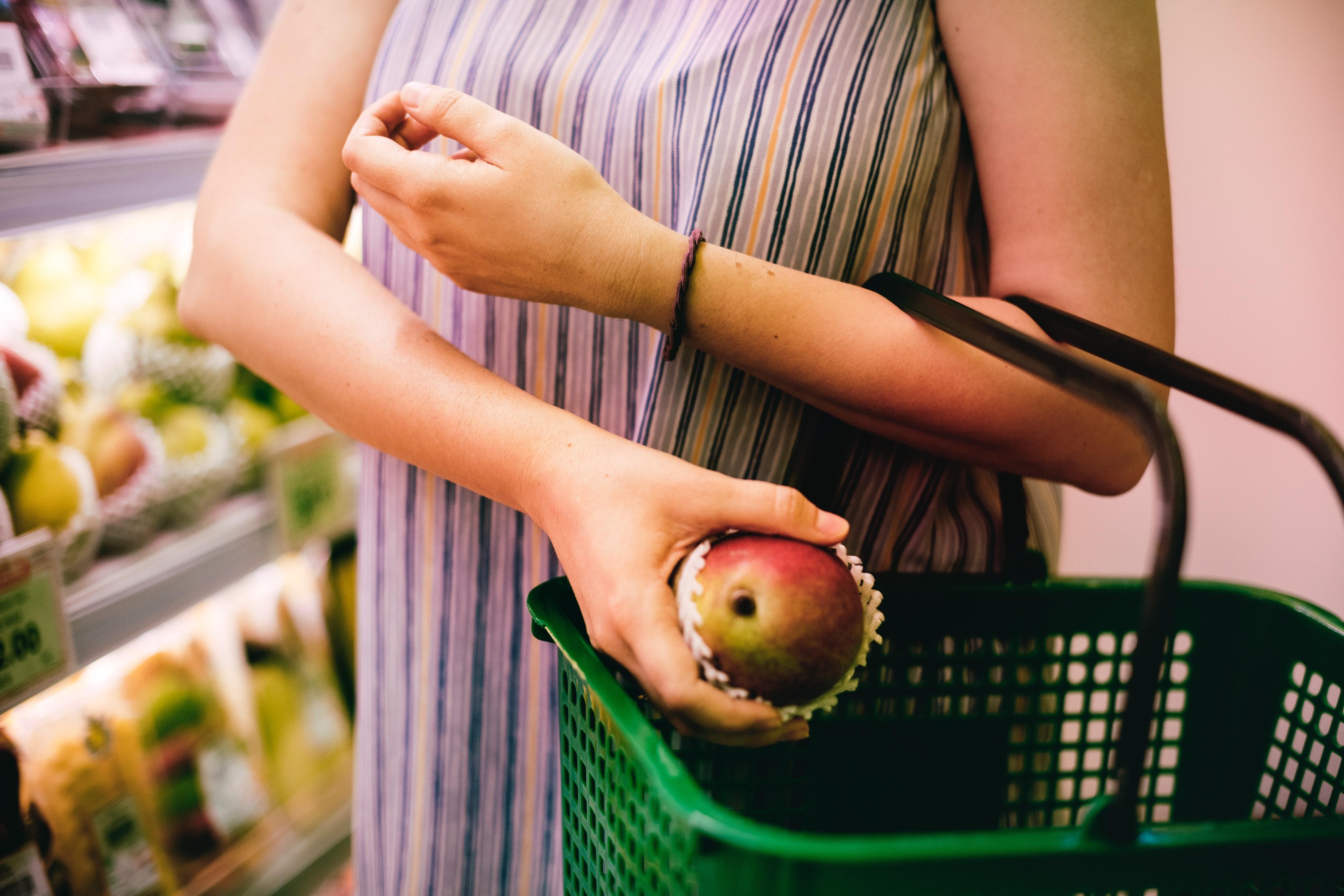 woman putting mango in a shopping basket