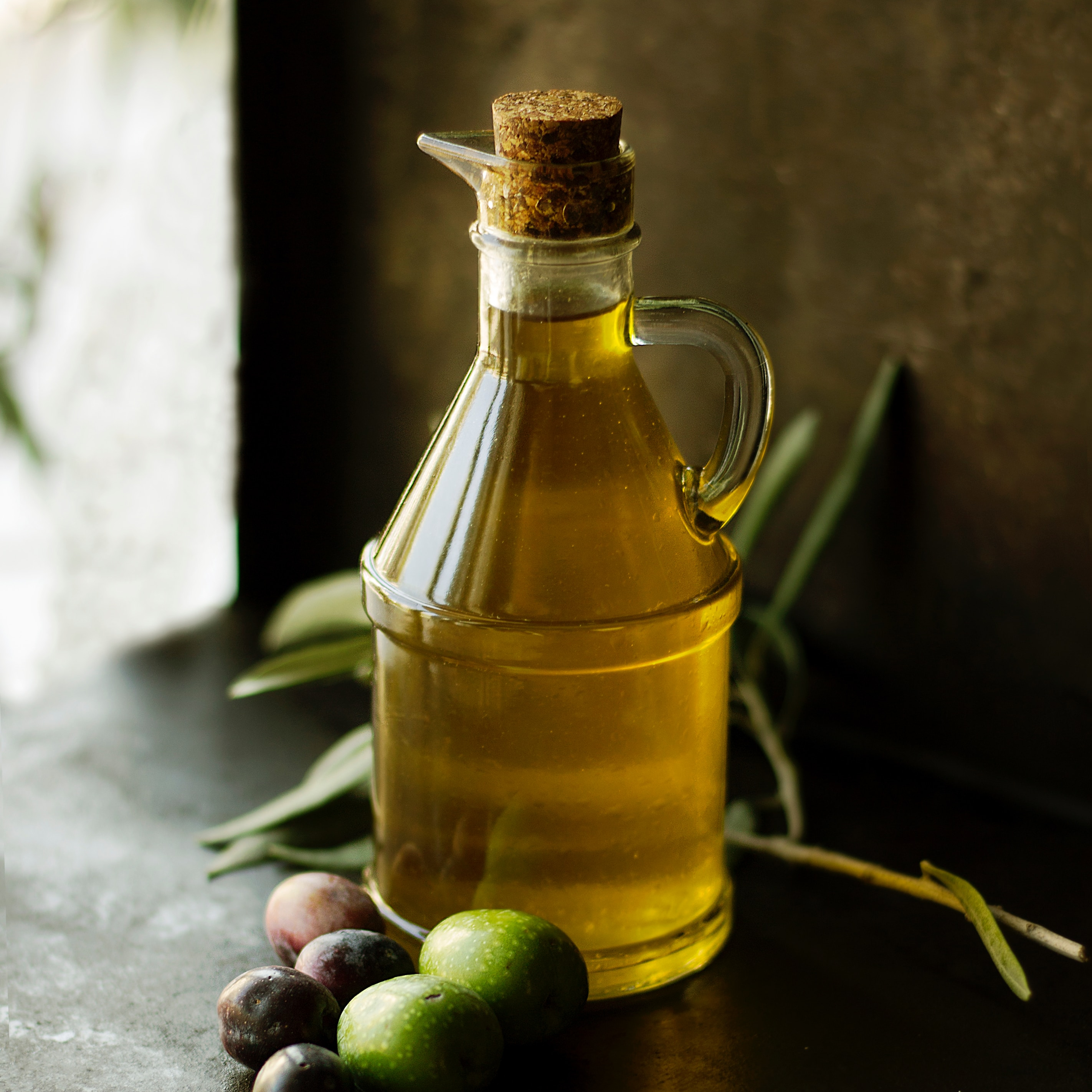 bottle of olive oil with olives in a dark room