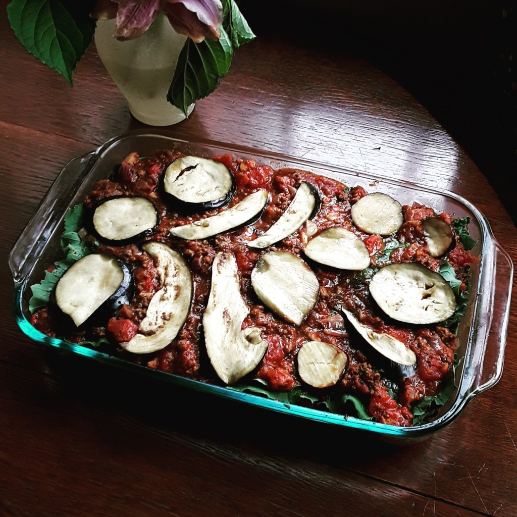 eggplant lasagna without cheese in a casserole dish near a vase