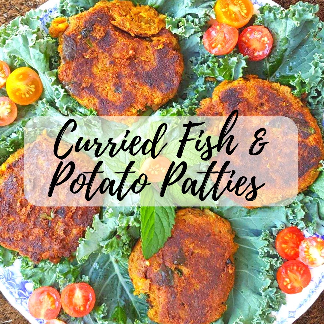 curried fish and potato cakes on a bed of kale with tomatoes